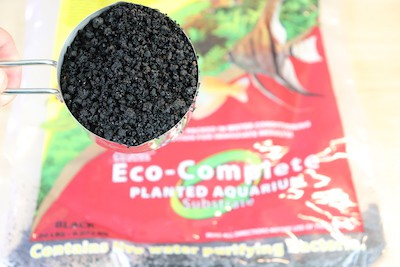 Eco Complete aquarium substrate in a measuring cup. Eco Complete's texture is grainy and its particle sizes vary.